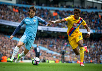 David Silva and Wilfried Zaha challenge for the ball